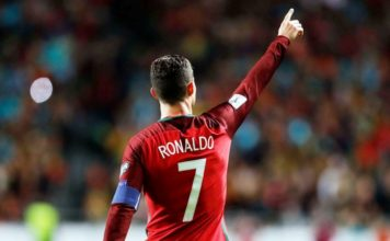Portugal captain and number 7 icon Cristiano Ronaldo carries his national team's armband on his left arm and points his right finger at the crowd.