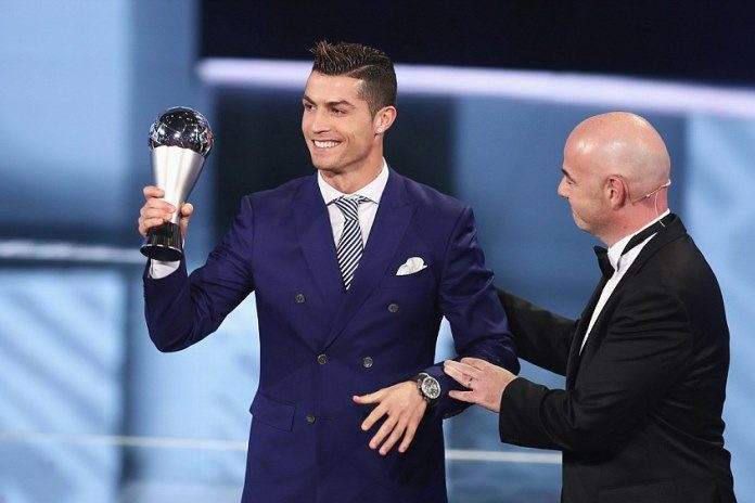 Cristiano Ronaldo lifts the 2016 Best FIFA Men's award as Gianni Infantino congratulates him.