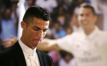 Cristiano Ronaldo nods his head down during his Real Madrid contract renewal. A Cristiano Ronaldo poster of him in a Real Madrid shirt is in the background.